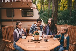 Happy family on a camping trip relaxing in the autumn forest. Camper trailer. Fall season outdoors trip