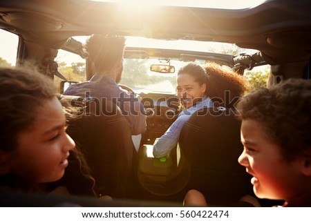 Happy family on a road trip in their car, rear passenger POV