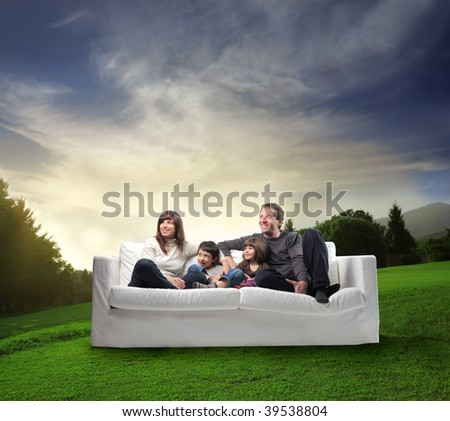 happy family on a sofa in a beautiful natural landscape
