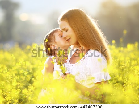 Happy family on a summer meadow. little girl child daughter hugging and kissing mother