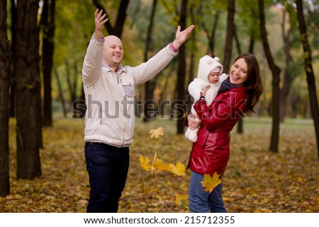Happy family on autumn walk in the park. Husband leaves wife showered with baby yellow leaves
