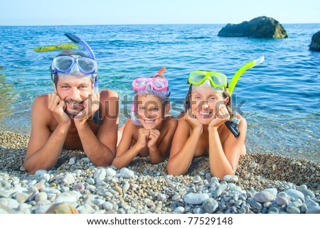 Happy family on beach with snorkles ready to have a good time swimming