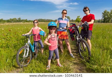 Happy family on bikes, cycling outdoors. Active parents and kids on bicycles. Family sport and fun, healthy lifestyle concept