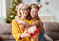Happy family on Christmas morning. Affectionate grandmother and cheerful granddaughter open a holiday gift together at home