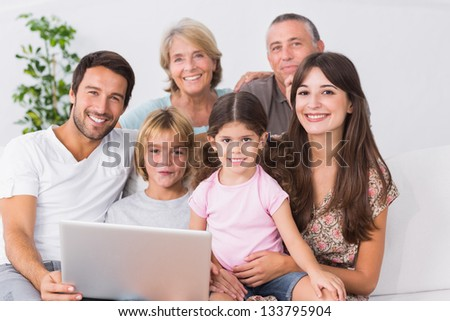 Happy family on couch using laptop in the living room