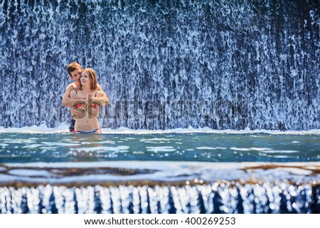 Happy family on honeymoon holidays - just married couple embracing and swimming with fun in waterfall pool. Active lifestyle, people outdoor travel activity on summer vacation on tropical Bali island. #400269253