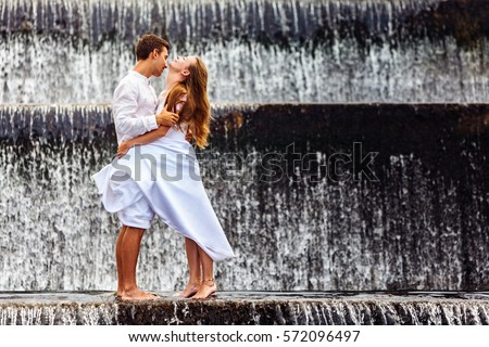 Happy family on honeymoon holidays - married loving couple hugging, kissing with fun under falling water in cascade waterfall pool. Active lifestyle, people travel on summer vacation on Bali island