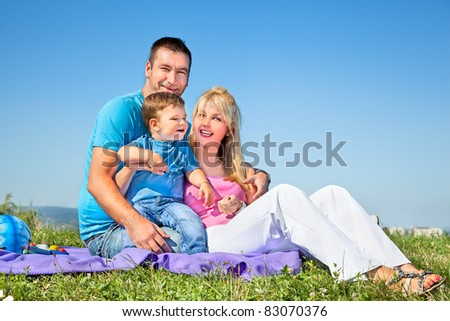 Happy family on picnic in park under blue sky