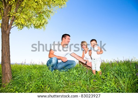 Happy family on picnic in park under tree