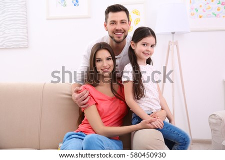 Happy family on sofa at home #580450930