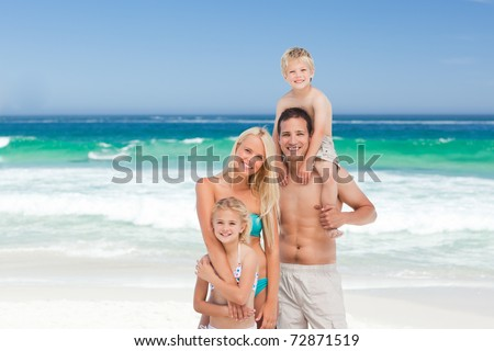 Happy family on the beach - stock photo