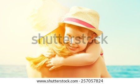 happy family on the beach. baby girl hugging her mother at the sea