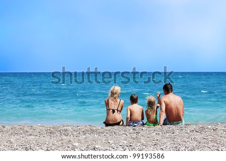 Happy family on the beach. Mother dad daughter and son sitting back on beach