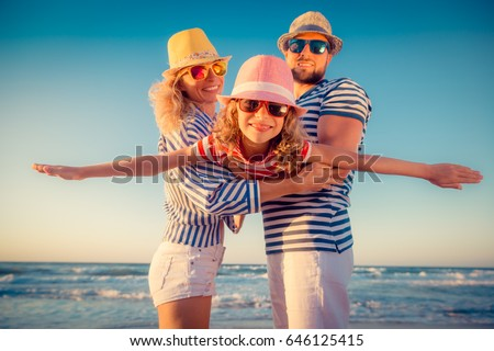 Happy family on the beach. People having fun on summer vacation. Father, mother and child against blue sea and sky background. Holiday travel concept #646125415