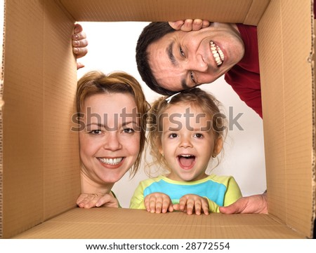 Happy family opening cardboard box - moving concept