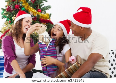 happy family opening Christmas gift at home