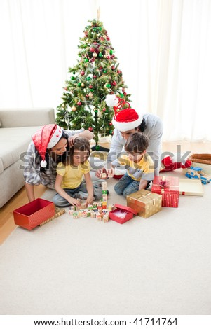 Happy family opening Christmas presents in the living-room