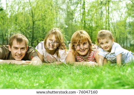 Happy Family outdoor lying on a green grass
