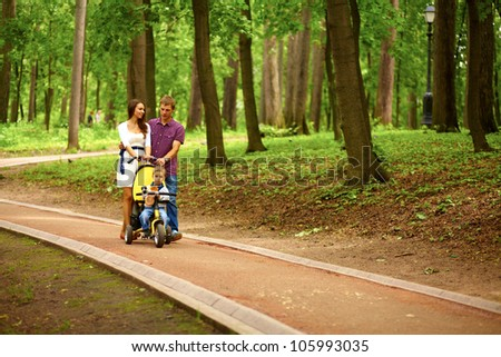 Happy family outdoor - mother, father and boy are smiling in baby carriage - stock photo