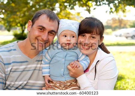 Happy family outdoor - mother, father and son are smiling