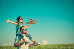 Happy family outdoors. Child playing with father. Dad and son having fun in summer field. Man carrying kid. Child with toy airplane. Kid pretend to be pilot. Travel, vacation and freedom concept
