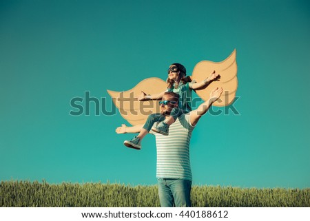 Happy family outdoors. Child playing with father. Dad and son having fun in summer field. Man carrying kid. Child with cardboard wings. Kid pretend to be pilot. Imagination and freedom concept