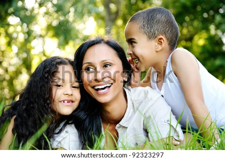 happy family outdoors on the grass in a park. mom and two children smiling