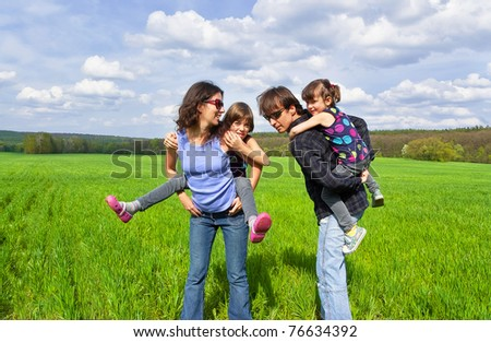 Happy family outdoors. Parents giving their kids piggyback ride - stock photo