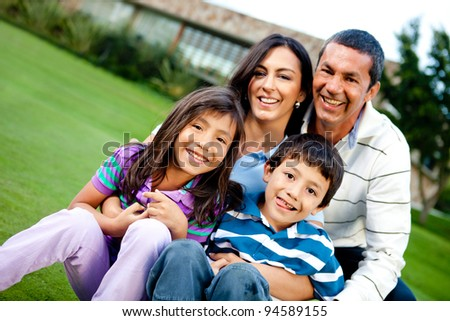 Happy family outdoors with a house at the background