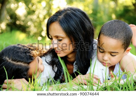 Happy family outsoors on the grass in a park, smiling faces all lying down having fun