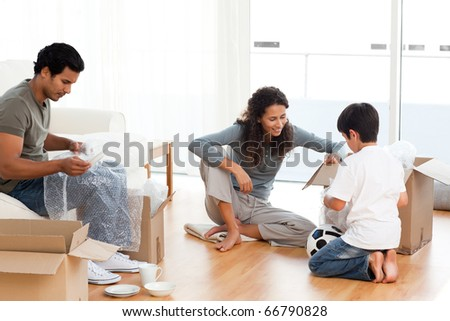 Happy family packing dishes together in their living-room for their removal