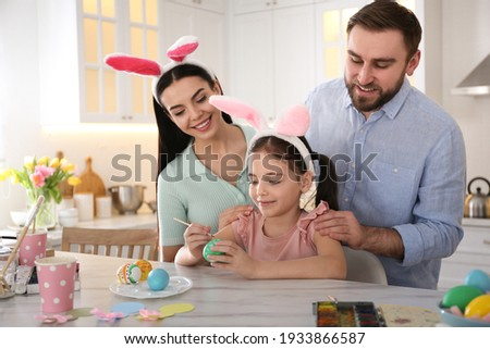 Happy family painting Easter eggs at table in kitchen