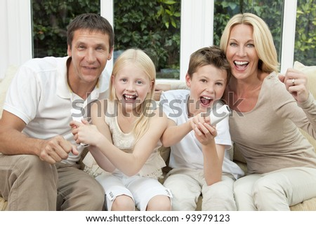 Happy family, parents, son and daughter, having fun playing video console together, the children have the remote controls, the parents are cheering.