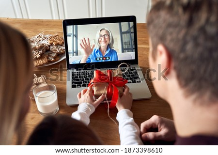 Happy family parents with kid child daughter holding Christmas gift greeting old senior grandparent on laptop screen having virtual party dinner on video conference call celebrating holiday together.