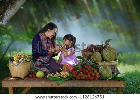Happy family picking fresh organic fruits on a farm,Mom and Daughter harvest of fruit at the farm,Thai organic fruits farm,thailand,