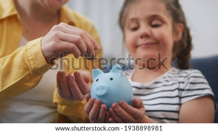 happy family piggy bank. mom and daughter future a put coins in the piggy bank. mortgage loan savings home in crisis coronavirus concept. happy family hoarding money in a piggy bank