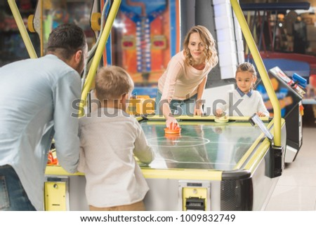 happy family playing air hockey together in entertainment center   #1009832749