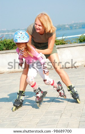 happy family playing and skating  on her in-line rollerblade skates