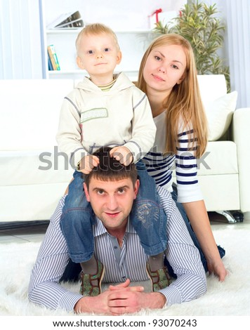 Happy family playing at home, lying heaped on floor in living room