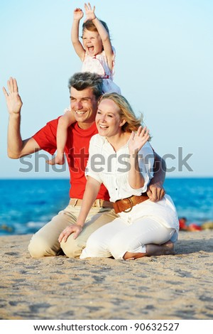 Happy family playing at red sea beach during sunset