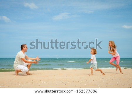 Happy family playing at the beach in the day time