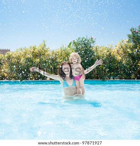 Happy family playing in blue water of swimming pool on a tropical resort at the sea. Summer vacations concept