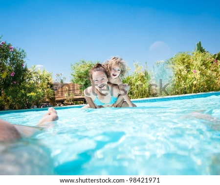 Happy family playing in swimming pool on a tropical resort at the sea. Summer vacations