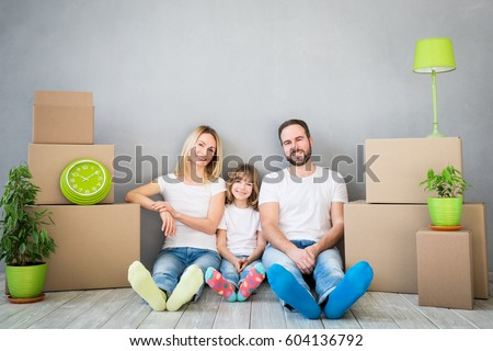 Happy family playing into new home. Father, mother and child having fun together. Moving house day and real estate concept