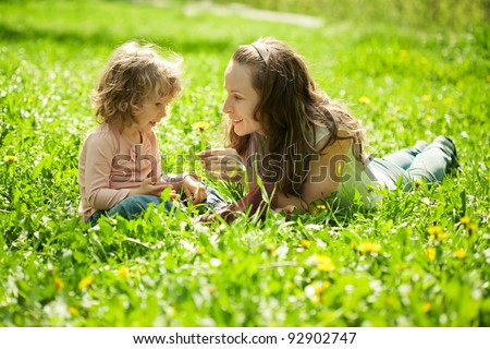 Happy family playing on green grass in spring park