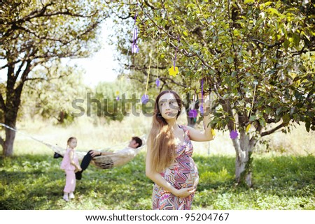 happy family playing on the lawn next to the hammock in the garden. Beautiful pregnant girl standing by a tree