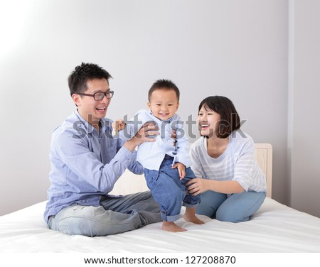 happy family playing on white bed in the bedroom at home, asian people