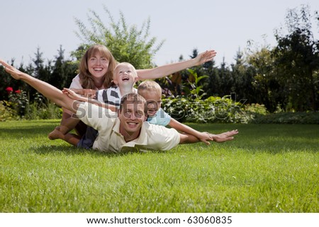 Happy family playing outdoors - stock photo