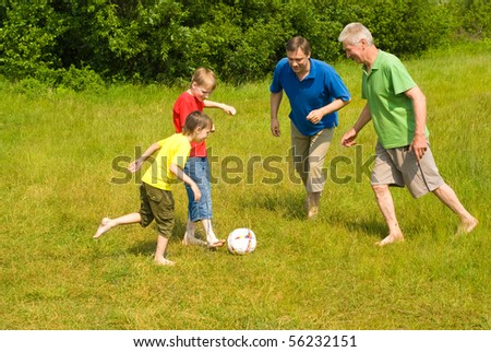 happy family playing soccer on the grass
