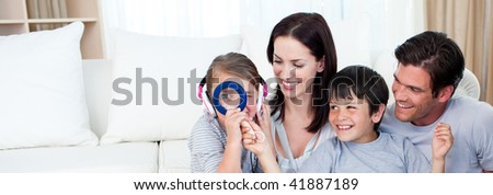 Happy family playing with a magnifying glass in the living-room